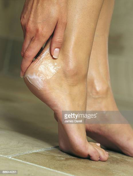 hand rubbing cream on heel - dressed undressed women stock pictures, royalty-free photos & images