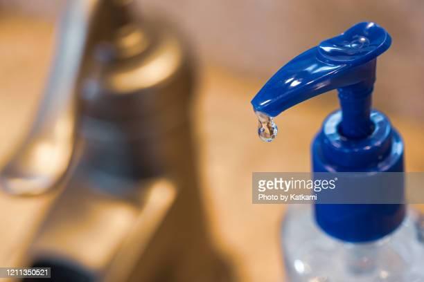 hand sanitizer bottle in front of a sink - hand sanitizer stockfoto's en -beelden
