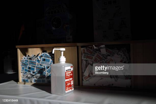 """Hand sanitizer bottle in front of """"omikuji"""" fortune strips at the Kanda Myojin shrine on the first business day of the year in Tokyo, Japan, on..."""