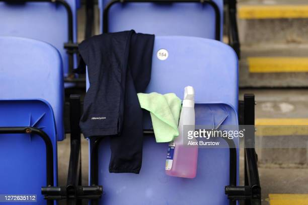 A hand sanitizer bottle is seen with a cloth on a seat inside the stadium prior to Carabao Cup Second Round match between Reading FC and Luton Town...
