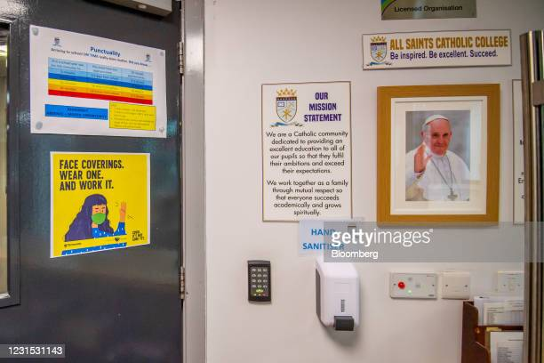 Hand sanitizer dispenser below a portrait of the Pope Francis at All Saints Catholic College in Dukinfield, Great Manchester, U.K., on Friday, March...