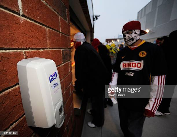 A hand sanitizer is mounted near a concession stand as soccer fans wear protective masks during a match between the Chicago Fire and Club America...