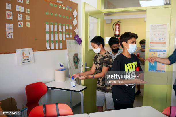 Hand sanitizer is put on students' hands before entering the classroom during the first day of school at Vedruna Angels School in Raval neighborhood...