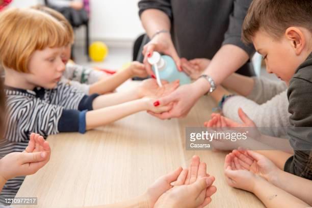 desinfetante de mão usado para proteger crianças no ensino fundamental - grupo médio de pessoas - fotografias e filmes do acervo