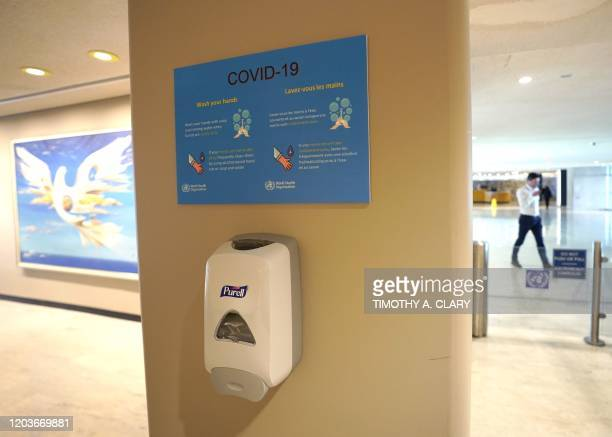 Hand sanitizers hang on the wall with a sign about COVID19 also known as coronavirus from the UN World Health Organization at the United Nations...