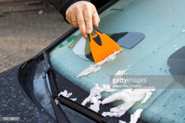 hand scraping ice off windshield - scraping stock photos and pictures