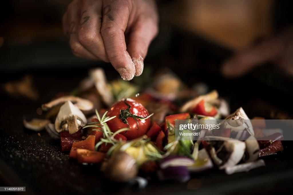Hand seasoning vegetables ona a baking tray : Photo