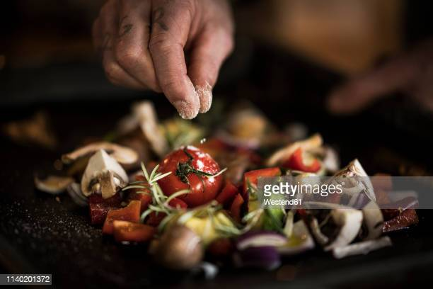 hand seasoning vegetables ona a baking tray - nahaufnahme stock-fotos und bilder