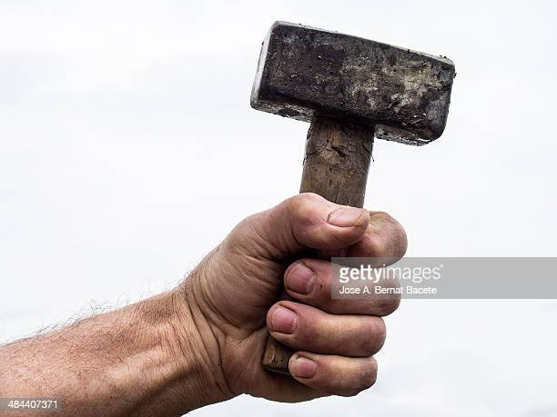 Hand seizing strongly a hammer