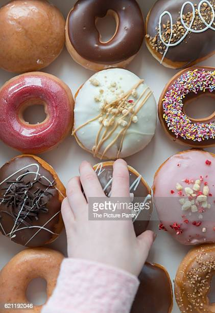 A hand selecting a donut from a box of a dozen donuts.