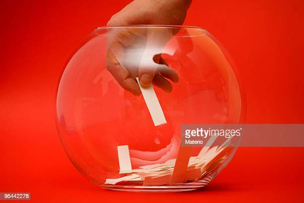 A hand selecting a paper ballot from a glass bowl on red