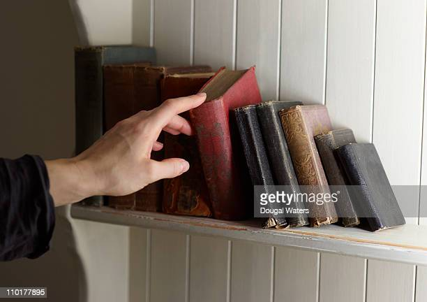 Hand selecting book from shelf.