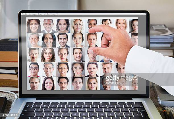 Hand selecting from portrait grid on laptop screen