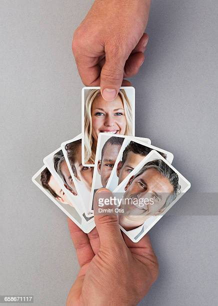 Hand selecting playing card with face from pack