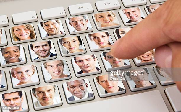 Hand selecting woman on keyboard of portraits