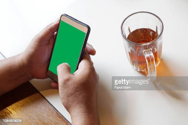 hand sending message on smartphone - iphone mockup stock pictures, royalty-free photos & images