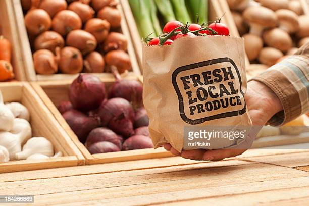 Hand serves a bag of fresh fruit and vegetables