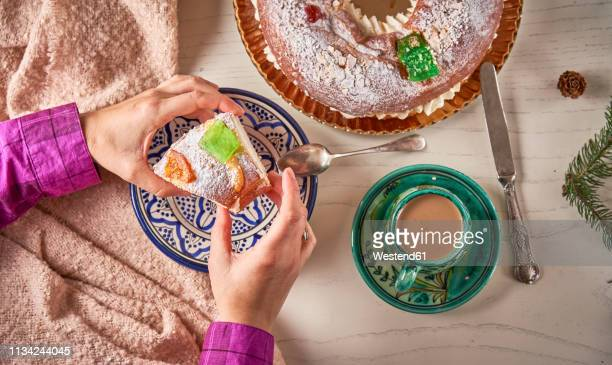 hand serving piece of spanish christmas cake - roscon de reyes stock pictures, royalty-free photos & images