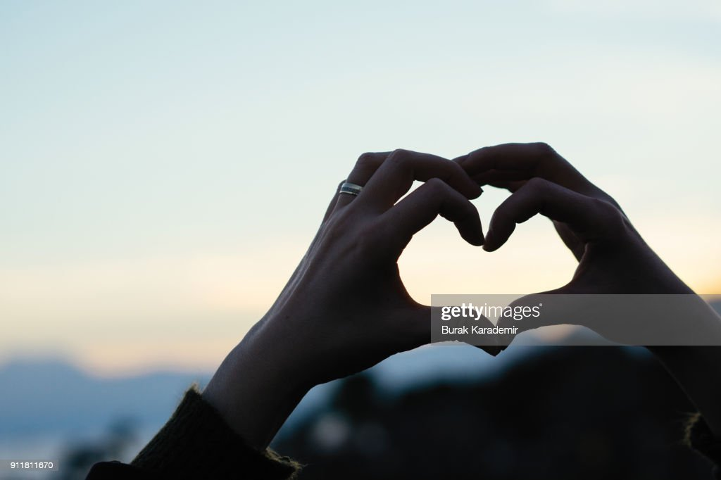 Hand shaped heart against sunset : Stock-Foto
