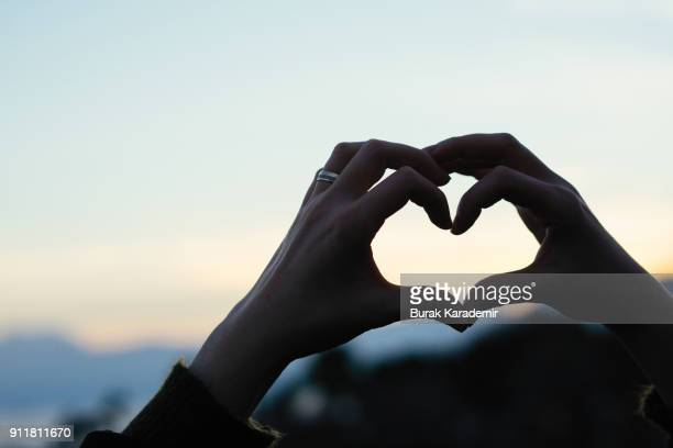 hand shaped heart against sunset - care stock pictures, royalty-free photos & images