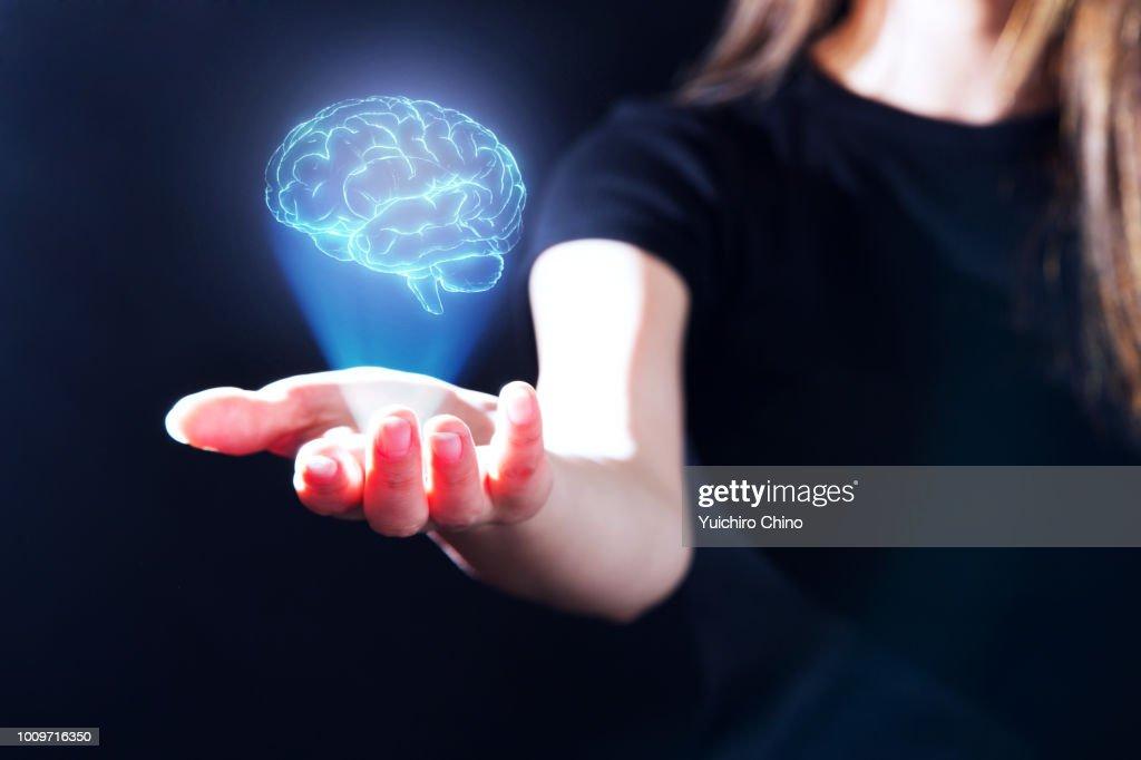 Hand showing a brain hologram : Foto de stock