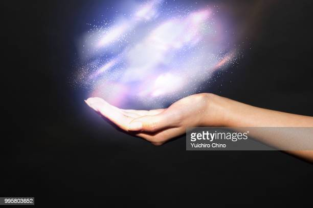 hand showing a galaxy - power in nature stock pictures, royalty-free photos & images