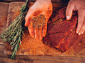 Hand showing spicy seasoning with a piece of raw pork