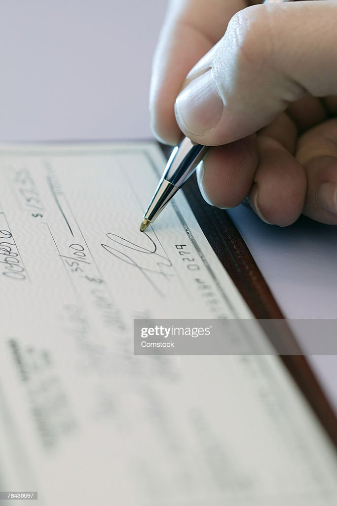 Hand signing a check : Stockfoto