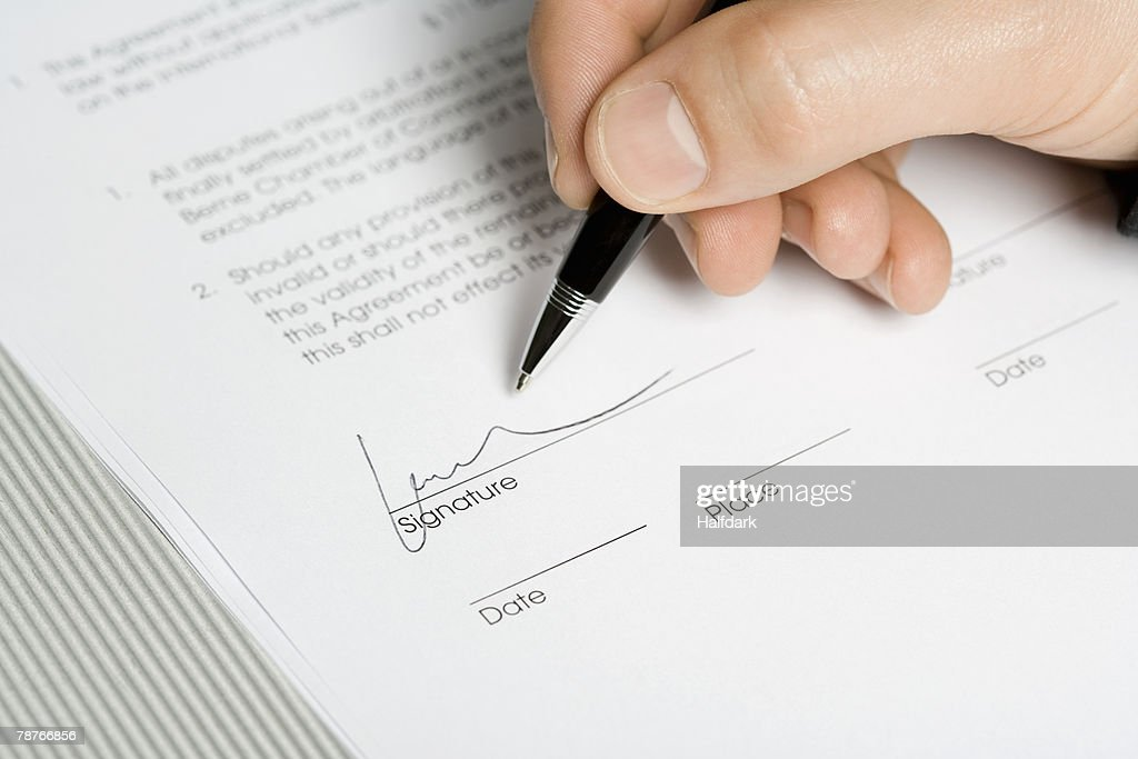 A hand signing a document : Stock Photo