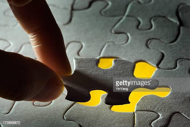 Main de résolution des problèmes, en installant pièce du Puzzle dans un jaune radieux