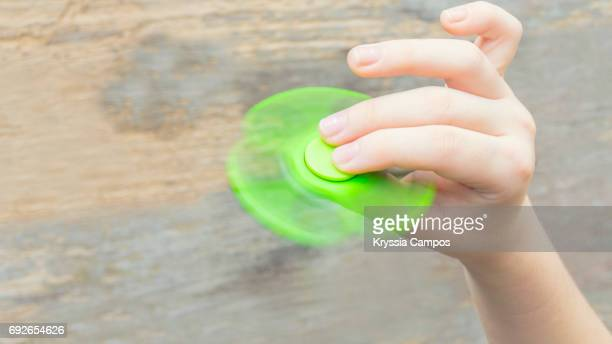Hand spinner, or fidgeting spinner, rotating on child's hand
