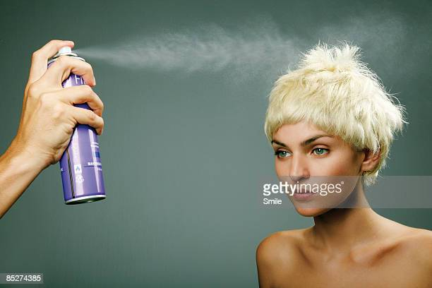 Hand spraying hair of young woman