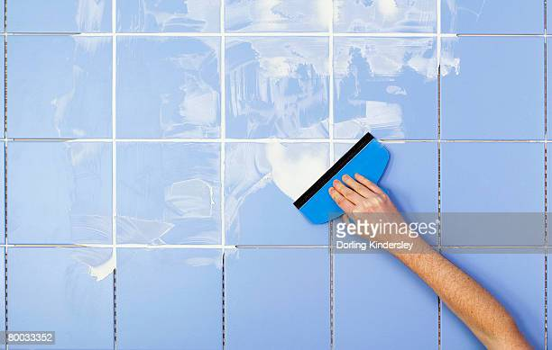 Hand spreading grout on tiles with grout spreader