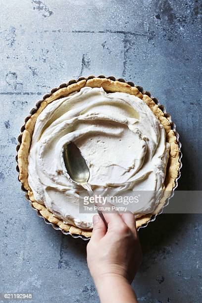 Hand spreading with the back of a spoon the whipped cream filling over the bottom of a tart.Top view