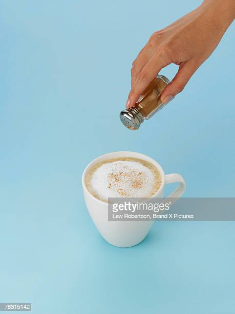 Hand sprinkling cinnamon onto cappuccino