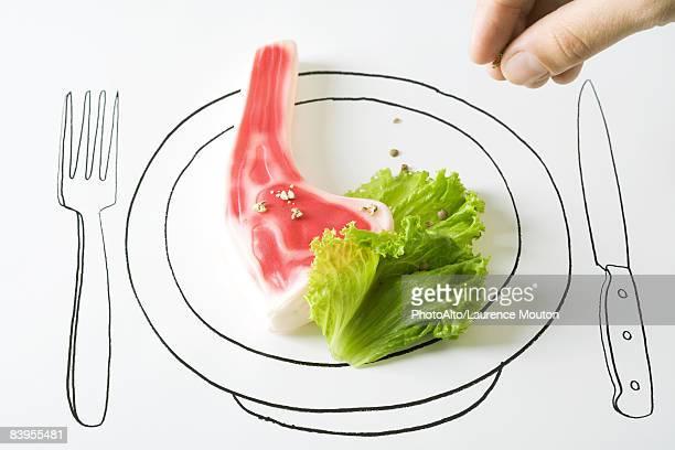Hand sprinkling peppercorns on plastic steak
