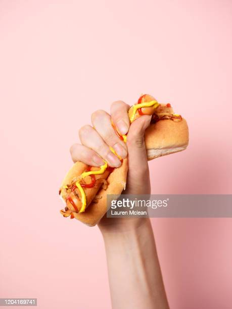 hand squeezing a hotdog - american culture stock pictures, royalty-free photos & images