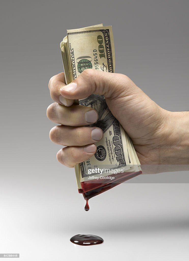 hand squeezing blood from money : Stock Photo
