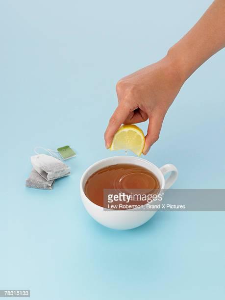 Hand squeezing lemon into tea