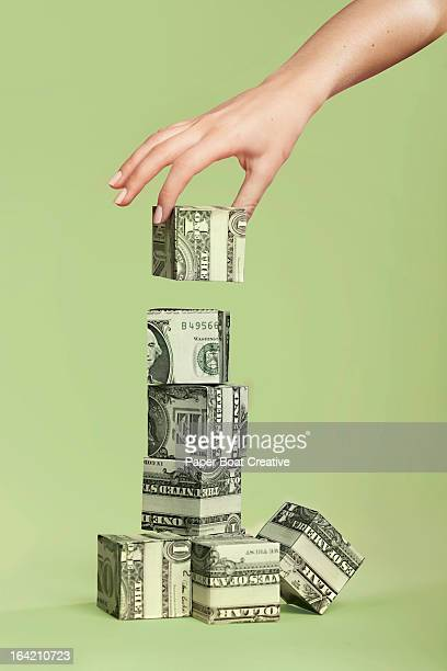 hand stacking up paper cubes made of dollar notes - american one dollar bill stock pictures, royalty-free photos & images