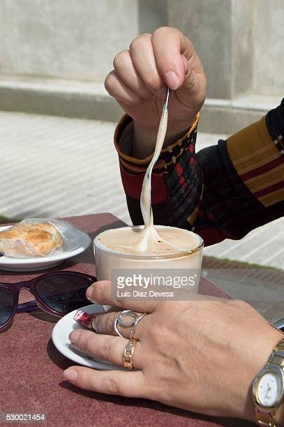Hand stirring a coffee with milk