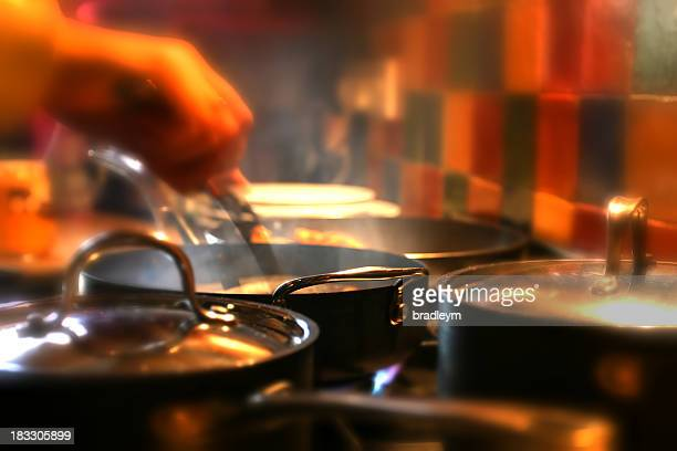 Hand stirring food in pan surrounded by other pots and pans