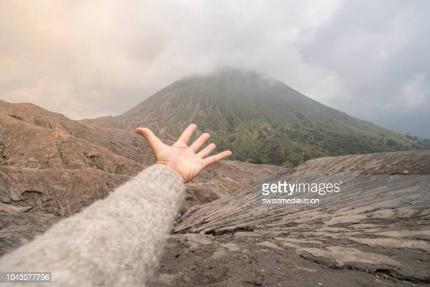 hand stretches towards volcano crater - bromo tengger semeru national park stock photos and pictures