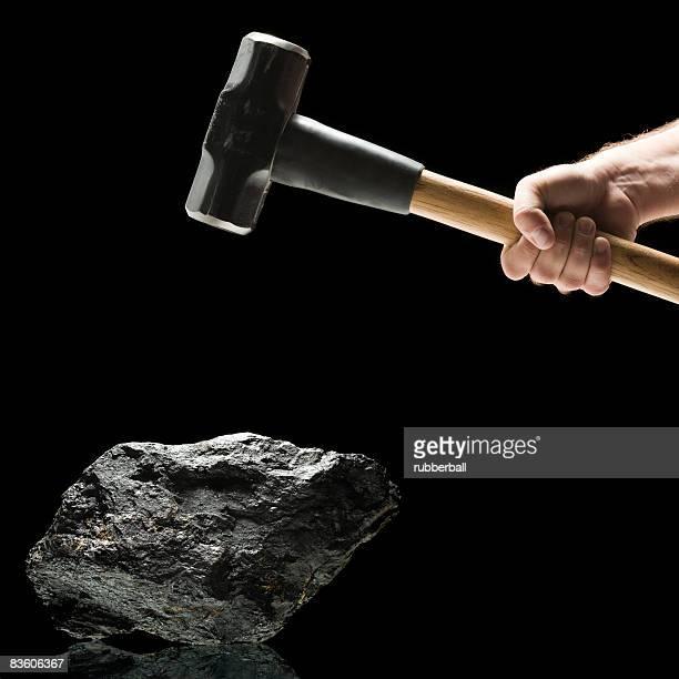 Hand swinging a sledge hammer toward a piece of coal.