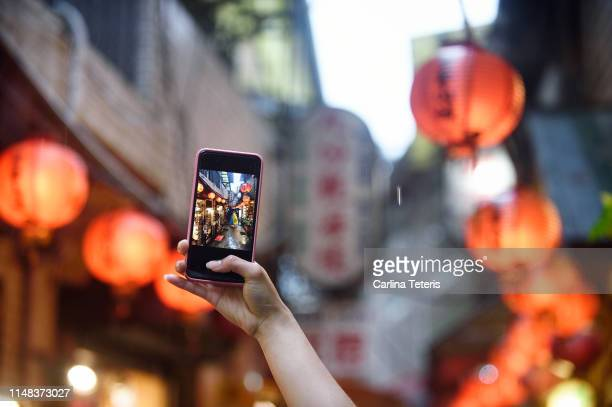 hand taking a picture of chinese lanterns with a smart phone - festival of remembrance 2019 stock photos and pictures