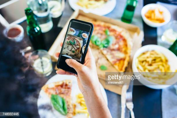 Hand taking cell phone picture of pizza on table