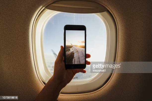 hand taking cell phone picture out of plane window - aircraft wing stock pictures, royalty-free photos & images
