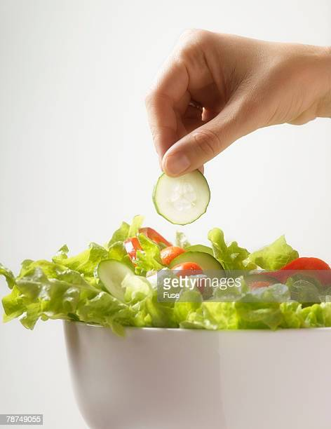Hand Taking Cucumber from Salad