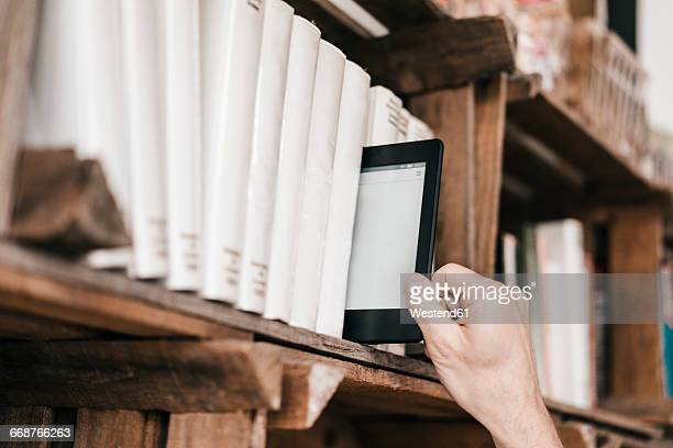 hand taking e-book from book shelf - e reader stock pictures, royalty-free photos & images