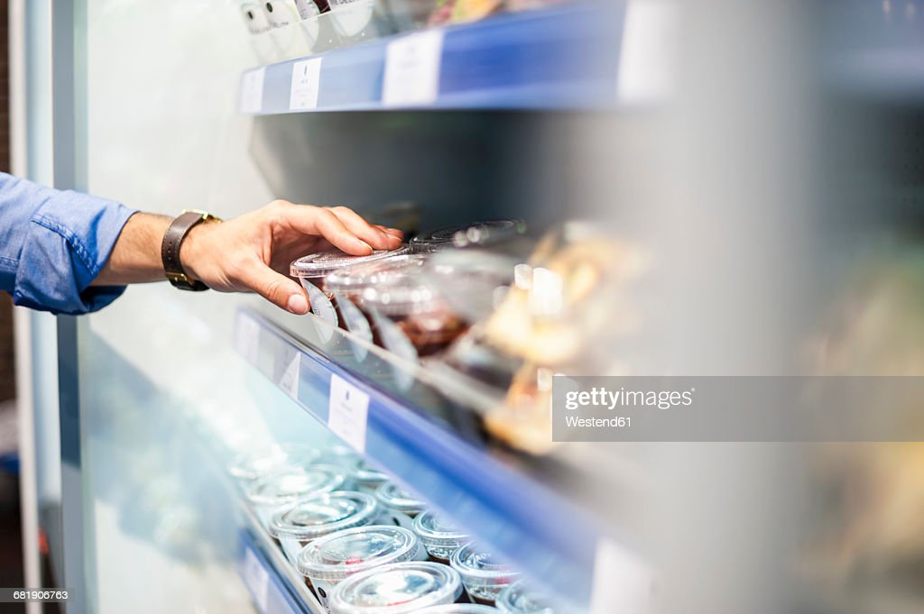 Hand taking food from cooling shelf : Stock Photo